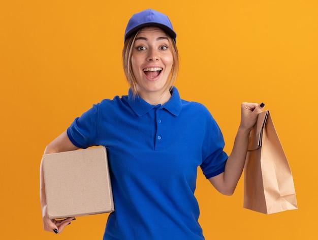La giovane ragazza graziosa di consegna emozionante in uniforme tiene il pacchetto di carta e il cardbox sull'arancia
