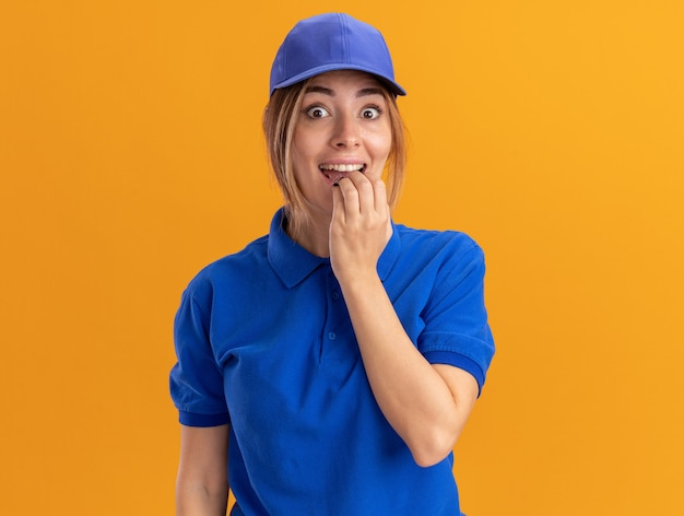 La giovane ragazza graziosa di consegna emozionante in uniforme mette la mano sulla bocca sull'arancia