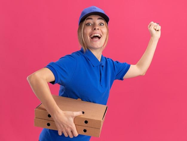 Eccitato giovane bella ragazza delle consegne in uniforme si leva in piedi lateralmente tenendo le scatole della pizza e tenendo il pugno sul rosa