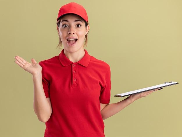 Eccitato giovane bella ragazza di consegna in uniforme si leva in piedi con la mano alzata e tiene appunti su verde oliva