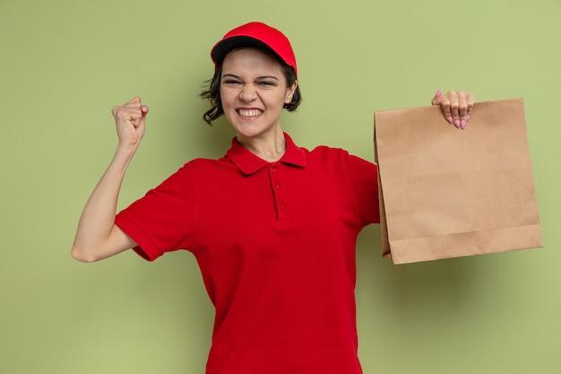 Eccitata giovane e graziosa donna delle consegne che tiene in mano imballaggi alimentari di carta e alza il pugno