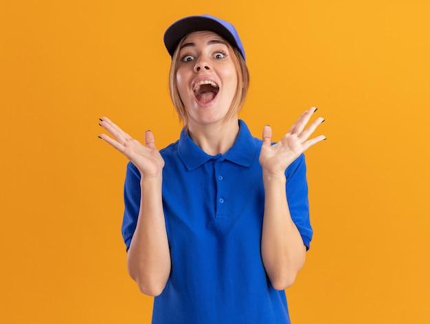 孤立した上げられた手を持った制服スタンドで興奮した若いかわいい配達の女性