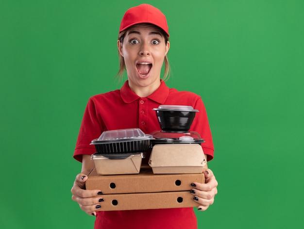 La giovane donna graziosa di consegna emozionante in uniforme tiene i pacchetti e i contenitori di cibo di carta sulle scatole della pizza isolate sulla parete verde