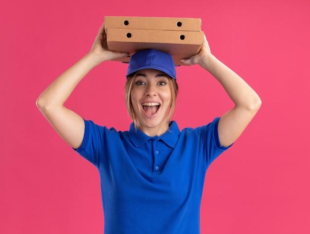 La giovane donna graziosa di consegna emozionante in uniforme tiene le scatole della pizza sopra la testa isolata sulla parete rosa