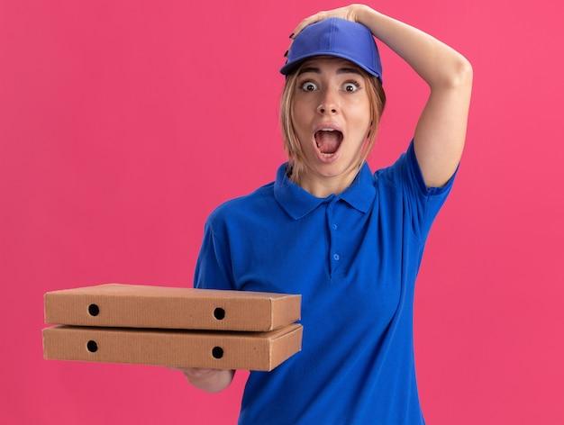 La giovane donna graziosa di consegna emozionante in uniforme mette la mano sul cappuccio e tiene le scatole della pizza isolate sulla parete rosa
