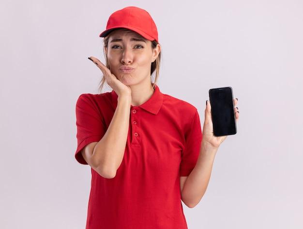 Eccitato giovane donna graziosa di consegna in uniforme mette la mano sul mento e tiene il telefono isolato sul muro bianco