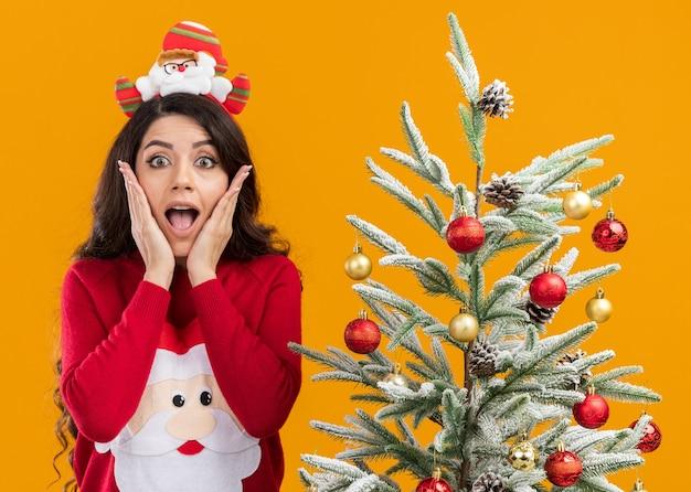 Возбужденная молодая красивая девушка в повязке на голову санта-клауса и свитере стоит возле украшенной елки, держа руки на лице, глядя в камеру, изолированную на оранжевом фоне