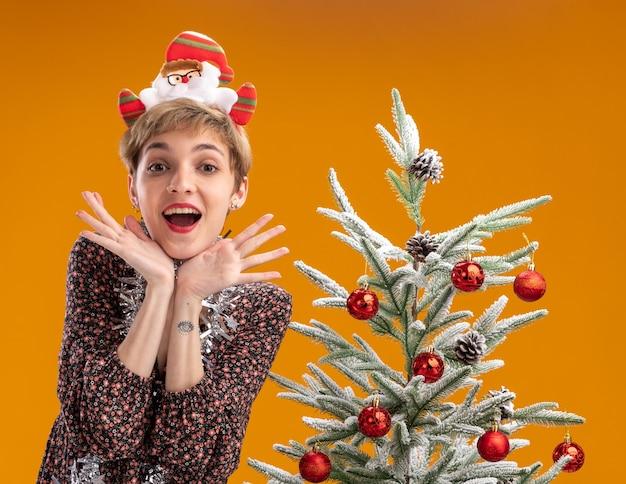 サンタクロースのヘッドバンドと首の周りに見掛け倒しの花輪を身に着けている興奮した若いかわいい女の子は、オレンジ色の背景で隔離の頭の下に手を置いてカメラを見ている装飾されたクリスマスツリーの近くに立っています