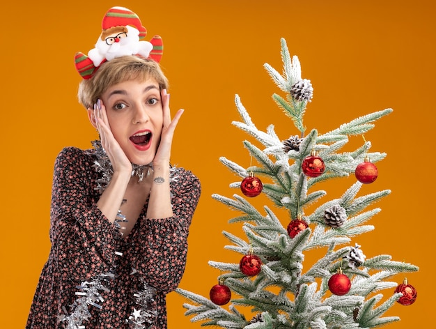 Excited young pretty girl wearing santa claus headband and tinsel garland around neck standing near decorated christmas tree looking at camera keeping hands on face isolated on orange background