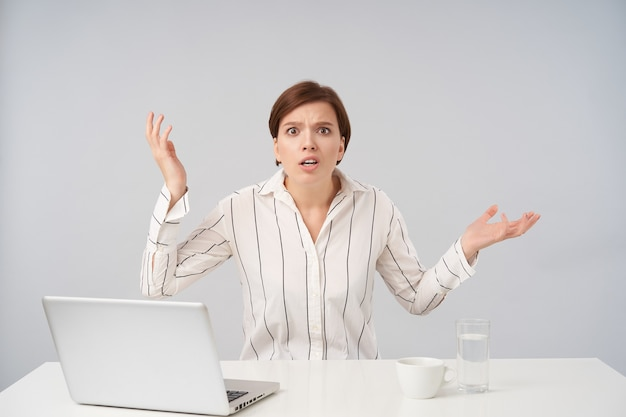 Eccitato giovane donna bruna dai capelli corti piuttosto vestita in camicia a righe bianche arrotondando perplessi i suoi occhi e sollevando emotivamente i palmi verso l'alto, seduto su bianco