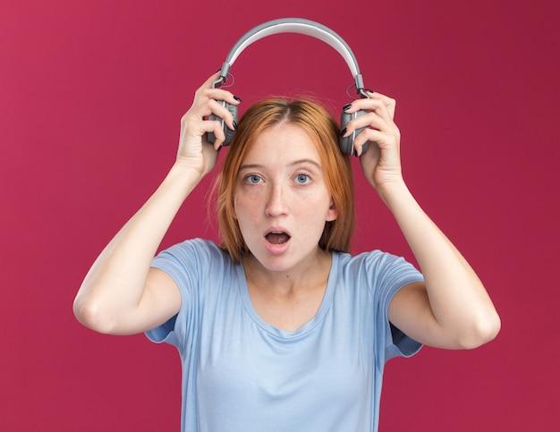 주근깨가 있는 흥분한 어린 빨간 머리 생강 소녀는 복사 공간이 있는 분홍색 벽에 격리된 머리 위로 헤드폰을 들고 있습니다