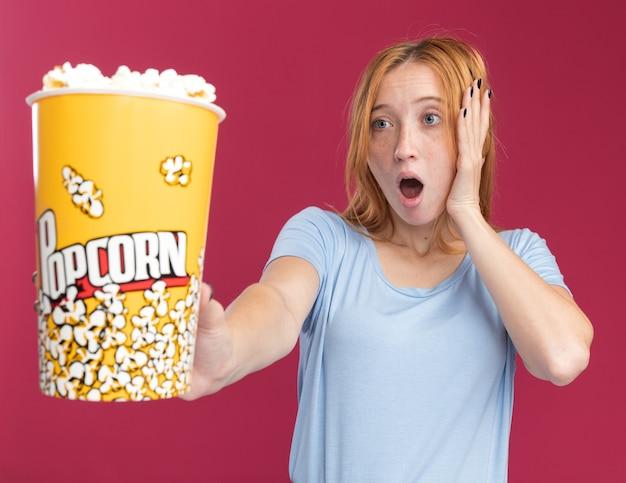 Eccitato giovane ragazza rossa dello zenzero con le lentiggini mette la mano sul viso che tiene e guardando il secchio di popcorn sul rosa