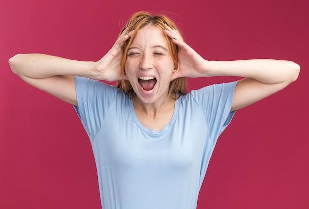 Eccitato giovane ragazza rossa zenzero con lentiggini in piedi con gli occhi chiusi tenendo la testa isolata sulla parete rosa con copia spazio Foto Gratuite