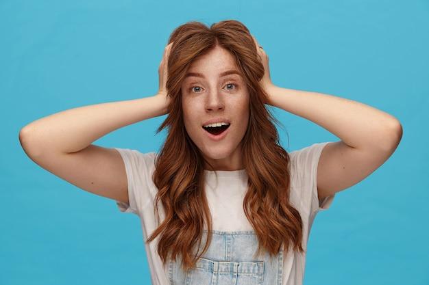 波状の髪型で興奮した若い赤毛の女性は、上げられた手で彼女の髪をつかんで、青い背景の上に立って、広い口を開いてカメラを見て