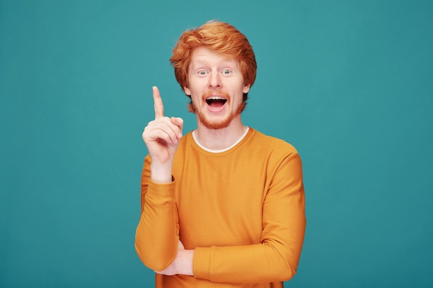 Excited young redhead man with beard having brilliant idea showing index finger on blue