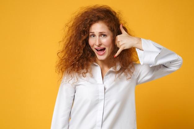 Eccitato giovane donna rossa ragazza in camicia bianca casual in posa isolata sul muro giallo arancione