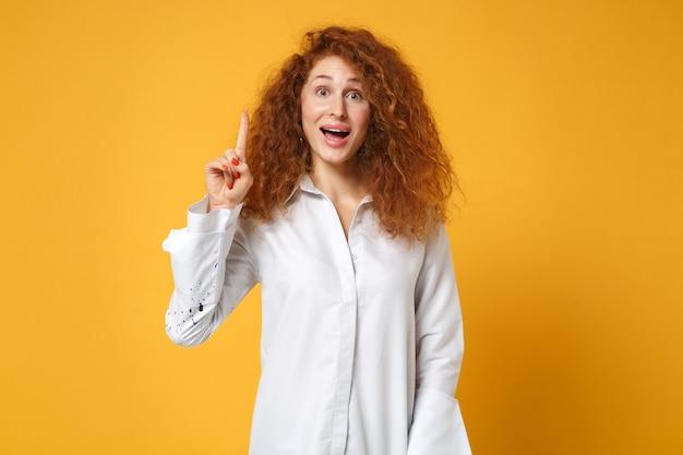 黄色のオレンジ色の壁に分離されたポーズのカジュアルな白いシャツで興奮した若い赤毛の女性の女の子