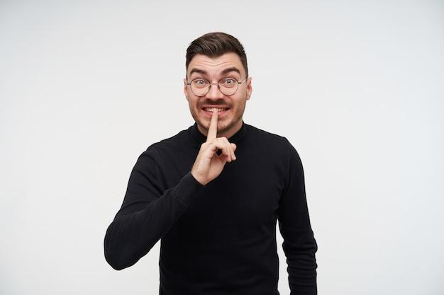 興奮した若い短い髪のひげを生やしたブルネットの男は、静かなジェスチャーで手を上げて興奮して見て、白い上に立っている間黒いセーターを着ています