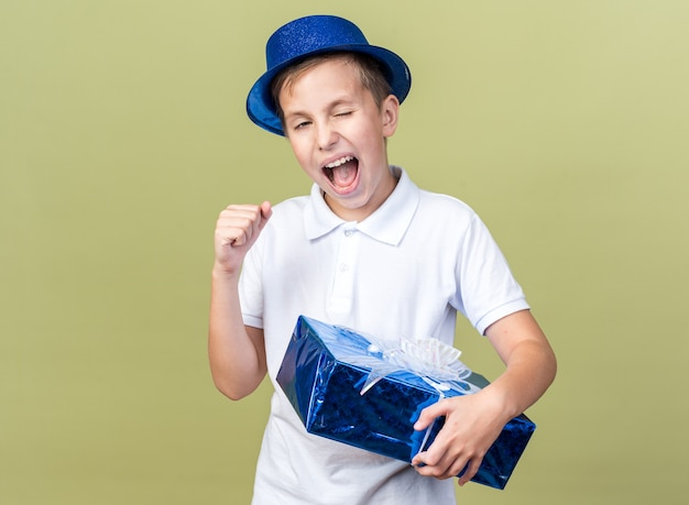Excited young slavic boy with blue party hat blinks his eye holding gift box and keeping fist up isolated on olive green wall with copy space
