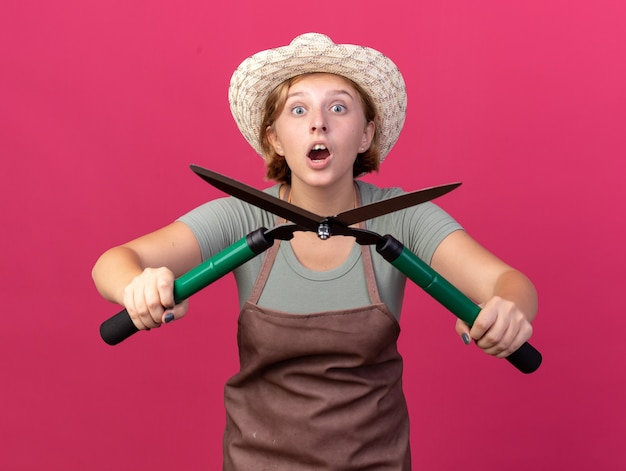 コピースペースとピンクの壁に分離されたガーデニングはさみを保持しているガーデニングの帽子と手袋を身に着けている興奮した若いスラブの女性の庭師