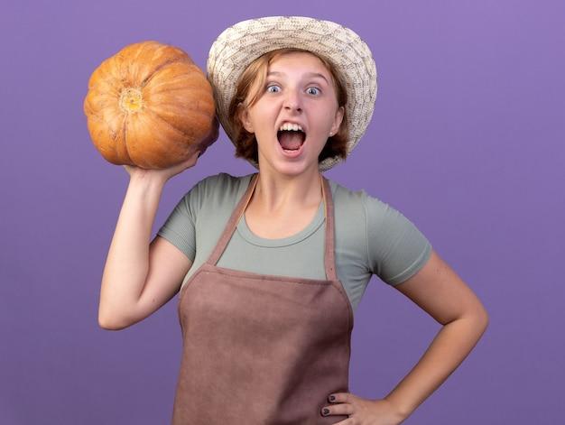 Eccitato giovane giardiniere femmina slava che indossa cappello da giardinaggio tenendo zucca