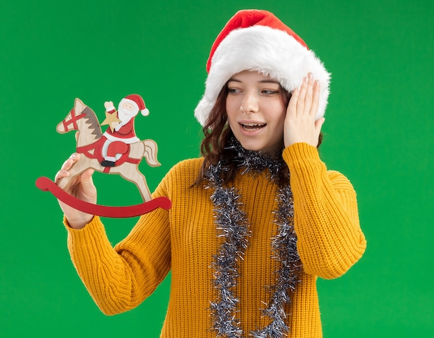 Excited young slavic girl with santa hat and with garland around neck holding and looking at santa on rocking horse decoration
