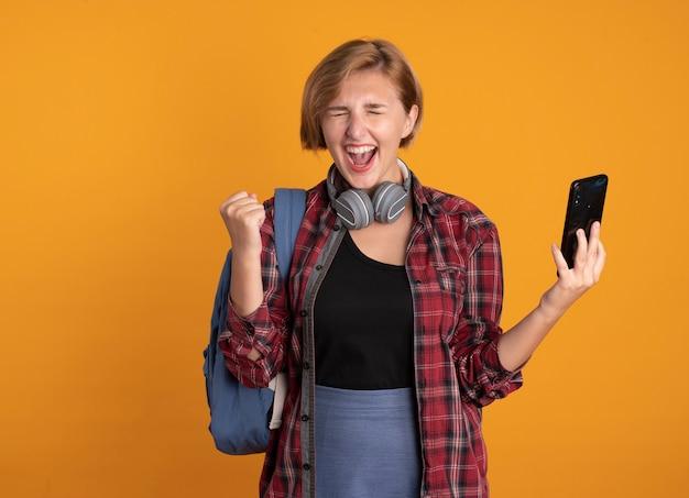 Una giovane studentessa slava eccitata con le cuffie che indossa lo zaino tiene il pugno e tiene il telefono
