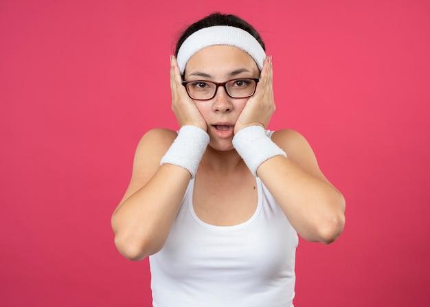 머리띠와 팔찌를 착용하는 광학 안경에 흥분된 젊은 스포티 한 소녀가 얼굴에 손을 넣습니다.