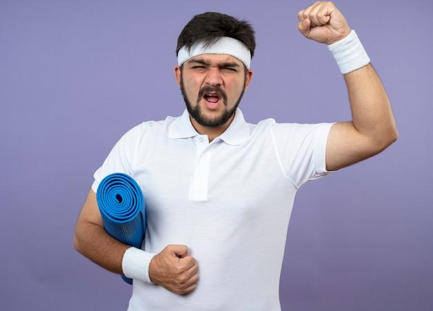 Взволнованный молодой спортивный мужчина с повязкой и браслетом, держащий коврик для йоги, показывает жест да, изолированный на зеленом