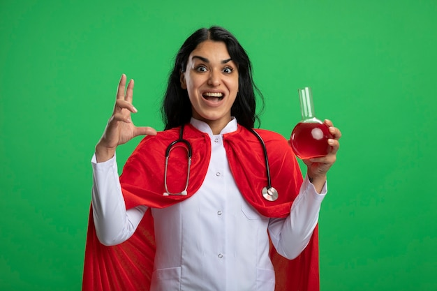 Eccitato giovane ragazza del supereroe che indossa una veste medica con lo stetoscopio che tiene la bottiglia di vetro di chimica riempita di liquido rosso e che mostra la dimensione isolata sul verde