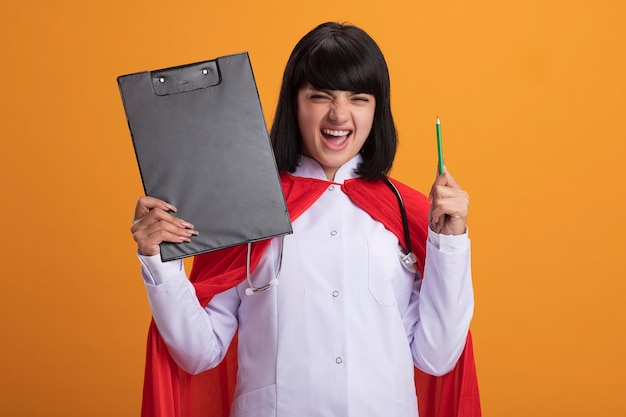 Eccitato giovane ragazza del supereroe che indossa uno stetoscopio con abito medico e mantello che tiene appunti con la matita isolata sull'arancio