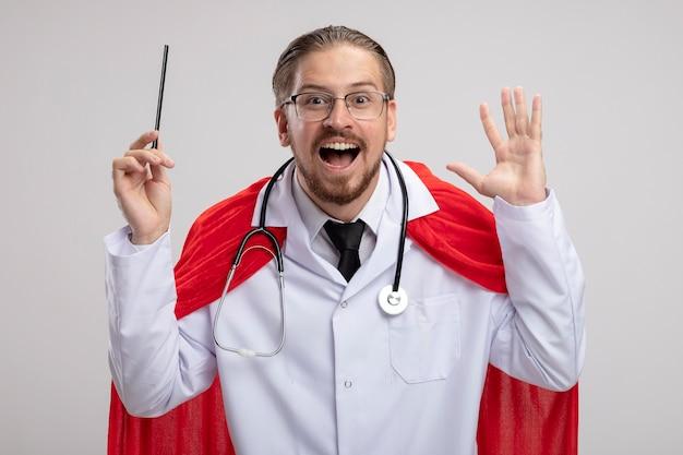 청진 기 및 흰색 배경에 고립 된 연필 올리는 안경 의료 가운을 입고 흥분된 젊은 슈퍼 히어로 남자