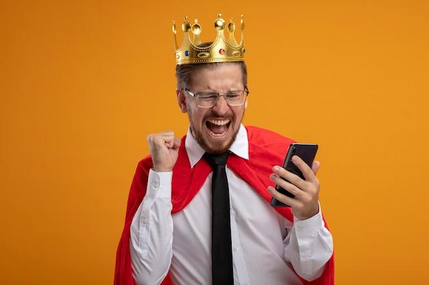 ネクタイと王冠を身に着けて、オレンジ色の背景に分離されたはいジェスチャーを示す電話を見て興奮している若いスーパーヒーローの男