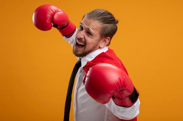 Eccitato giovane supereroe ragazzo indossa cravatta e guantoni da boxe in piedi in posa di combattimento isolato su sfondo arancione