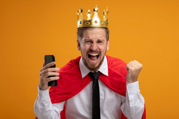 Excited young superhero guy wearing tie and crown holding phone showing yes gesture isolated on orange background
