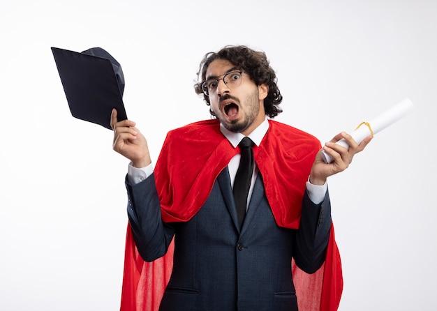 赤いマントとスーツを着て光学メガネで興奮した若いスーパーヒーローの男は、白い壁に分離された卒業証書と卒業証書を保持します