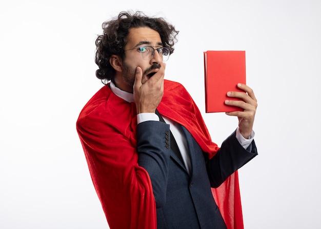 赤いマントとスーツを着て光学メガネで興奮した若いスーパーヒーローの男は、口に手を置き、白い壁に隔離された本を保持します。