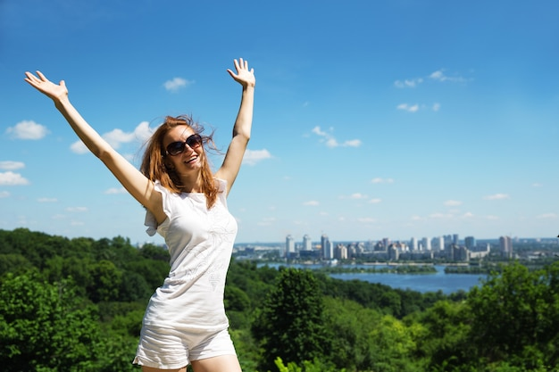 Excited young woman against cityscape