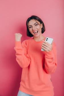 Giovane donna eccitata stupita dall'incredibile messaggio di vendita di app mobile per lo shopping guardando smartphone, vincitore della ragazza che tiene il telefono cellulare che grida di gioia