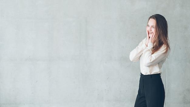 Возбужденная молодая женщина. красивая женщина смотрит на виртуальную рекламу руками на лице