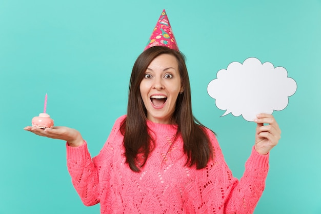 Excited young woman in birthday hat hold in hand cake with candle empty blank say cloud speech bubble for promotional content isolated on blue background. people lifestyle concept. mock up copy space.