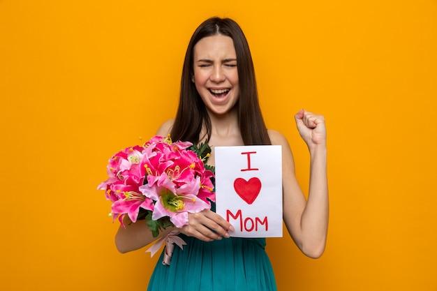 Eccitata giovane donna che celebra la festa della mamma, con in mano un biglietto di auguri e un bouquet