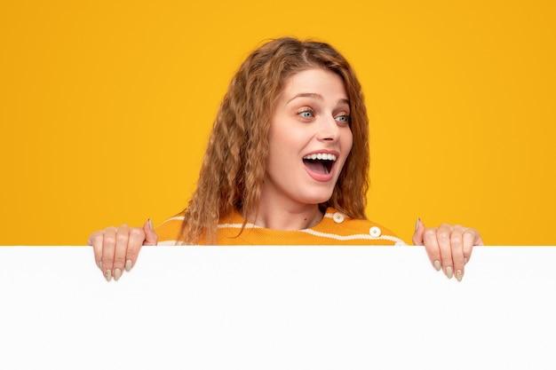空のバナーを示す興奮した若い女性