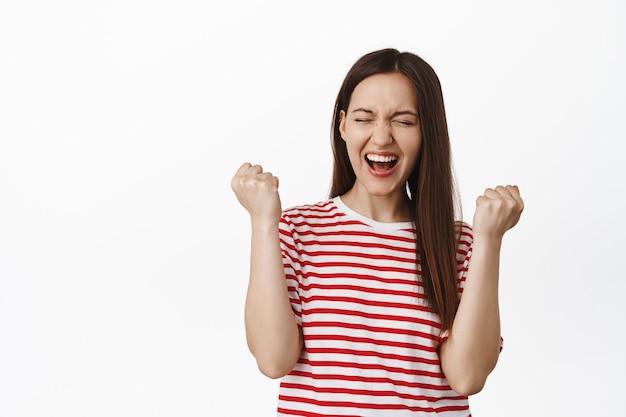 흥분한 젊은 여성 주먹 펌프, 예를 외치고 승리하는 여성, 목표 달성, 승리 축하, 흰색 벽에 티셔츠를 입고 서 있는