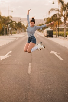 Excited young woman gesturing peace sign wearing roller skate jumping on road