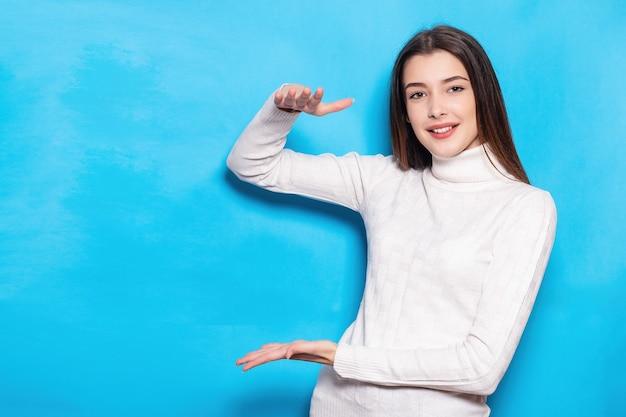 푸른 청록색 벽 배경에 격리된 캐주얼 화이트포즈를 입은 흥분된 젊은 여성 소녀. 사람들이 라이프 스타일 개념입니다. 복사 공간을 비웃습니다. 수직 작업 공간으로 크기를 보여주는 제스처