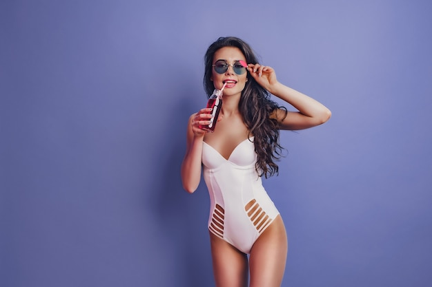 Excited young woman girl in white one-piece swimsuit, sunglasses posing with beverage isolated on purple background.