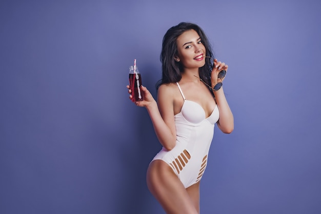 Excited young woman girl in white one-piece swimsuit, sunglasses posing with beverage isolated on purple background