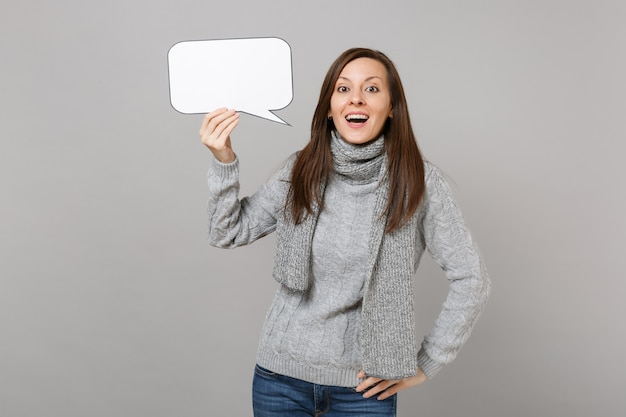 Excited young woman in gray sweater, scarf holding empty blank say cloud, speech bubble isolated on grey background. healthy fashion lifestyle people emotions, cold season concept. mock up copy space.