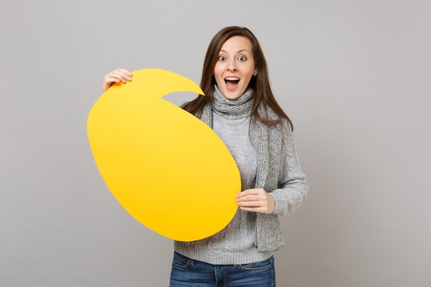 Excited young woman in gray sweater, scarf holding yellow empty blank say cloud speech bubble isolated on grey wall background. healthy fashion lifestyle, people sincere emotions, cold season concept.